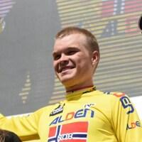 Il est sur le podium avec des fleurs et son maillot jaune.
