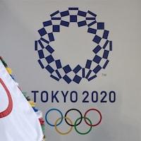 Le drapeau olympique flotte devant le logo des JO japonais.