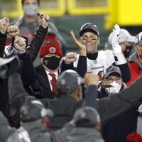 Un joueur au milieu du podium entouré de son équipe.