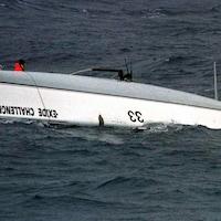 Tony Bullimore en orange, en mer, à côté de son navire chaviré