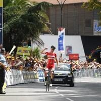 Un cycliste lève le bras en triomphe.