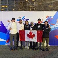 Des athlètes et des entraîneurs prennent une photo avec un drapeau du Canada.