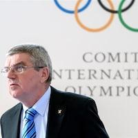 Il regarde au loin, les anneaux olympiques derrière lui.