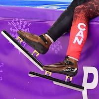 Gros plan sur les patins d'un athlète assis sur le bord de la bande.