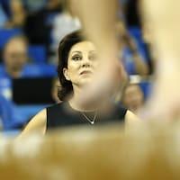 Une entraîneuse de gymnastique regarde le programme de l'une de ses athlètes à la poutre.