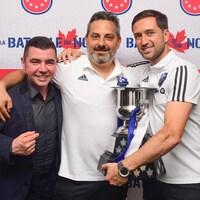 Trois hommes prennent la pose avec la coupe du Championnat canadien remporté par l'Impact en 2019.
