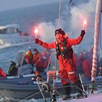 Le marin, sur son bateau, célèbre son arrivée avec des fusées éclairantes.