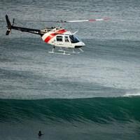 Un hélicoptère surveille les concurrents lors d'une compétition de surf en Australie.