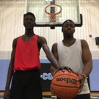 Deux joueurs des Coyotes posent, ballon à la main, devant un panier de basketball