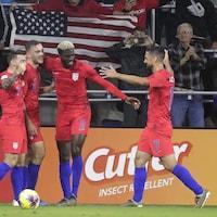 Quatre joueurs des États-Unis se félicitent.