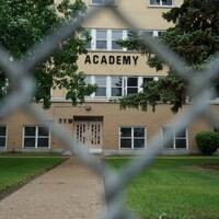 Une vue de près sur l'Académie Rivier prise à travers d'un grillage.