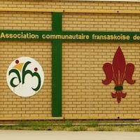 L'enseigne de l'Association communautaire fransaskoise de Moose Jaw sur un mur de brique jaune.