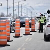 Un policier signale une voiture qui approche un contrôle routier.