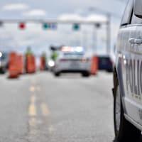 """La mise au point sur le mot """"police"""" sur la porte d'une auto-patrouille avec en arrière plan un barrage routier."""