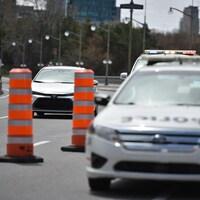 Une voiture s'approche d'une auto-patrouille arrêté sur le pont.