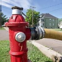 Une borne-fontaine rouge avec un boyau jaune attaché après.