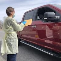Une infirmière tend une enveloppe à l'occupant d'un camion.
