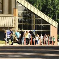 Des dizaines de personnes attendent leur tour d'entrer dans le bâtiment.