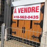 Une grosse affiche « À Vendre » avec un numéro de téléphone est collée sur la porte de l'église, qui est entourée d'une clôture.