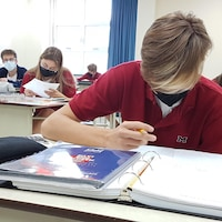 Un élève porte le couvre-visage en classe.