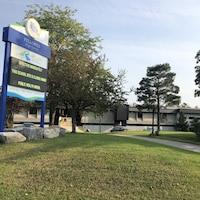 Affiche de l'école et l'édifice en arrière plan.