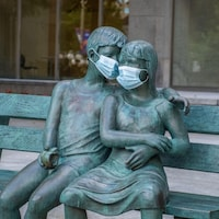 Sculpture d'un homme assis sur un banc avec une femme, le bras gauche de l'homme se trouvant sur les épaules de la femme. Des masques de procédures ont été mis pour couvrir les visages de la sculpture.
