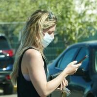 Une femme qui marche en regardant son cellulaire. Elle porte un couvre-visage.