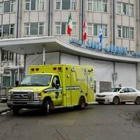 Entrée de l'Hôpital Santa Cabrini. Une ambulance est stationnée devant.