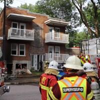 Des pompiers devant un immeuble ravagé par le feu.