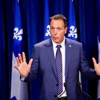 Le ministre Roberge, les mains levées, s'adressant aux journalistes à l'Assemblée nationale devant des drapeaux du Québec.