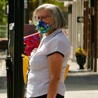 Une femme porte un masque à l'extérieur pendant la pandémie de la COVID-19 à Regina en l'été. (archives)