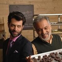 Une scène du film Peace by Chocolate montrant es acteurs syriens Ayham Abou Ammar et Hatem Ali tenant une plaque de chocolats.
