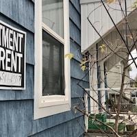 Une affiche annonce un appartement à louer, sur une maison.