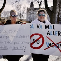Deux manifestantes portent des pancartes sur lesquelles est écrit : « Que faites-vous pendant que l'on a vraiment besoin de vous pour défendre nos droits et libertés » et « Ça va mal aller ».