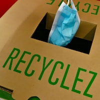 Un masque est jeté dans une boîte de recyclage.