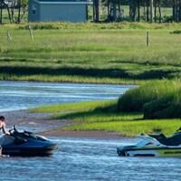 Deux hommes debout dans l'eau s'apprêtent à monter sur leurs motomarines.