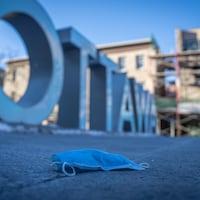 Un masque chirurgical sur le sol près des grosses lettres « OTTAWA ».
