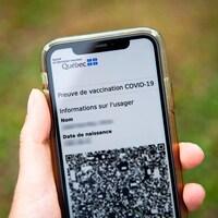 Quelqu'un tient un téléphone intelligent. On aperçoit la preuve vaccinale sur l'écran.