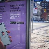 Une affiche de l'application Alerte COVID, sur un abribus dans le centre-ville d'Ottawa.