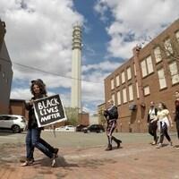 Un jeune homme avec une pancarte BLACK LIvES MATTER