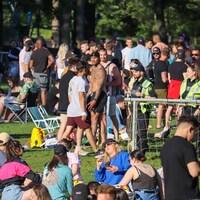 Deux policiers circulent parmi les personnes ressemblées dans le parc.