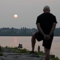Des personnes regardent le coucher de soleil près de la rivière des Outaouais.