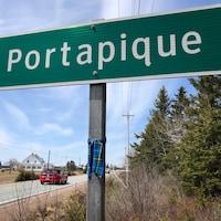 Tartan bleu et vert noué au poteau soutenant le panneau qui annonce l'entrée à Portapique, en bordure d'une route rurale.