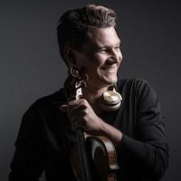 Un jeune homme souriant un violon à la main, des écouteurs suspendus au cou