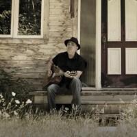 Le chanteur Florent Vollant avec sa guitare, assis sur un balcon