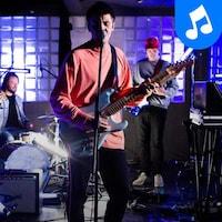 L'artiste et ses musiciens offrent une prestation dans un local montréalais.
