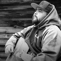 Photo noir et blanc. L'auteur-compositeur-interprète Matiu (Matthew Vachon) joue de la guitare assis sur une chaise devant une habitation de bois.
