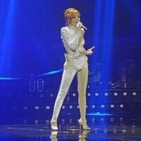 Mylène Farmer vêtue d'un costume blanc, brillant et moulant, sur une scène éclairée d'une lumière bleutée