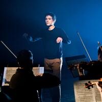 Le jeune chef d'orchestre Nicolas Ellis en train de diriger un orchestre dans les studios de Radio-Canada