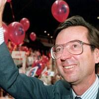 Portrait de Robert Bourassa qui salue une foule dans un congrès du Parti libéral.